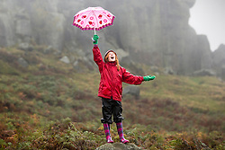 © Licensed to London News Pictures. 28/10/2015. Ilkley, UK. 10 year old Cerys add's a splash of colour to a bleak day in the rain on the Cow & Calf rocks at Ilkley Moor in Yorkshire. Photo credit: Andrew McCaren/LNP