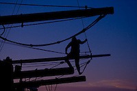 a crew member of the tall ship brig Lady Washington climbs out on a yardarm to do some work