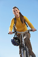 Young woman riding mountain bike low angle view.