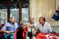"""AFFILE, ITALY - 23 AUGUST 2012: (L/R) Aldo Graziani (78), Giandomenico Abbafatt (43) and ex-mayor of Affile Diego Moriconi, 61, discuss about the collaboration with Nazis in World War II, in Affile, a town with a population of 1,600 80km east of Rome, on August 23, 2012. A mausoleum and park, dedicated to the memory of Fascist Field Marshall Rodolfo Graziani, has recently been opened in the Italian town of Affile. At a cost of €127,000 to local taxpayers, the mayor Ercole Viri has expressed hope that the site will become as 'famous and as popular as Predappio' – the burial place of Mussolini which has become a shrine to neo-Fascists. Rodolfo Graziani was the youngest colonel in the Regio Esercito (Royal Italian Army), known as the """"Butcher of Fezzan"""" and the """"Butcher of Ethiopia"""" for the brutal military campaigns and gas attacks he led in Libya and Ethiopia under the dictatorship of Benito Mussolini under which he then became Minister of Defence from 1943 to 1945."""