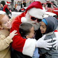 Santa Claus gives a group hug to children at Reed Park during Santa Monica Firefighters & Police Officers Association's Eighteenth  annual 'Candy Cane Drive' on Saturday, December 4, 2010.
