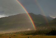 USA, Alaska, Girdwood, A double rainbow seen at sunrise over Moose Meadows, with Chugach State Park & the Chugach Mountains in the distance.