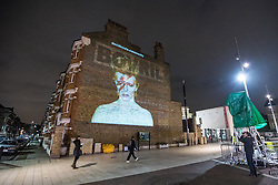 © Licensed to London News Pictures. 10/01/2017. London, UK. A projection of David Bowie lights up Windrush Square in Brixton, south London, on the first anniversary of the star's death. Bowie was born in Brixton and remains a local icon. Photo credit: Rob Pinney/LNP