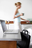 Woman in kitchen walking by laptop focus on laptop