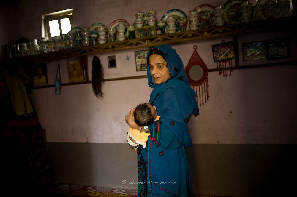 Ghair Bibi's daughter Kasbano holds her two-month-old baby boy. <br /> Her mother assisted the home delivery. <br /> A traditional midwife for over 40 years, Ghair Bibi most fondly remembers conducting the deliveries of her own family members. Karachi, Pakistan, 2011