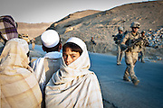 Afghan children look on as an American patrol passes.