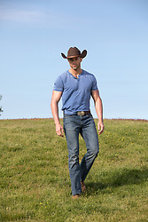 cowboy walking on a grassy hill