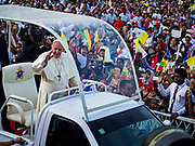 "29 NOVEMBER 2017 - YANGON, MYANMAR:  POPE FRANCIS, standing in the ""Popemobile,"" drives through the crowd at the Papal Mass in Yangon. Hundreds of thousands of Catholics from Myanmar attended the mass said by Pope Francis at Kyaikkasan Sports Ground in Yangon Wednesday. Pope Francis is on the first visit by a Pope to Myanmar.   PHOTO BY JACK KURTZ"