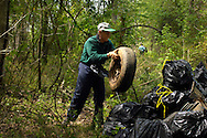 Volunteers pick up litter-- 80% plastic drink containers-- from an island in the Catawba River in Lancaster County, SC. Miles downstream from the City of Charlotte, trash litters the islands and shoreline. Upstream of the tributary which drains the City, there is hardly any trash.  For this clean-up event, Duke Energy sent a boat to pick up the trash bags, tires, and other items.