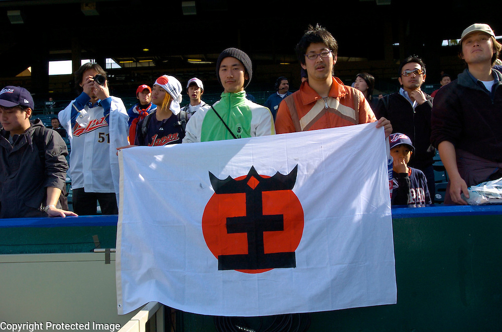 Team Japan fans hold a Japanese flag with Team Japan's manager Sadaharu Oh's last name before the start of the game against Team Mexico in Round 2 action at Angel Stadium of Anaheim.