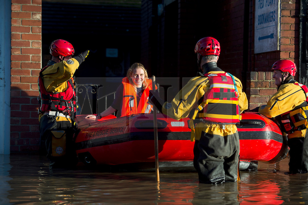 © Licensed to London News Pictures. 27/12/2015. York, UK.  A young woman being rescued from a  house on Huntingdon Road in York. Large areas of the North of England have been hit by severe flooding following unusually heavy rainfall in December. Photo credit: Ben Cawthra/LNP