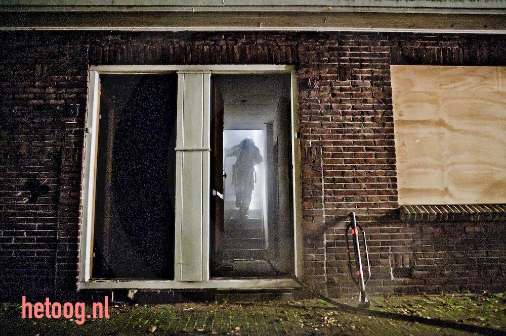 nederland enschede 03-10-2010 In de enschedese wijk velve lindenhof  wordt najaar 2010 veelvuldig brand gesticht in leegstaande te slopen huizen. een brandweerman heeft zich toegang verschaft door de voordeur te forceren.
