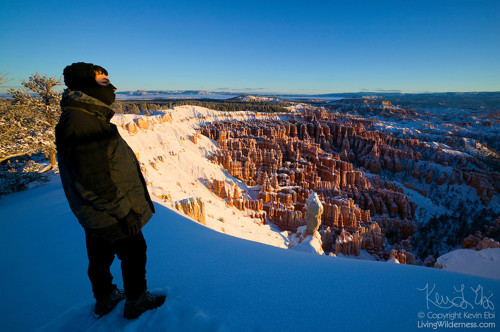 A hiker admires the view of the Bryce Canyon amphitheater in Utah on a cold winter morning after fresh snowfall. Winter temperatures in the canyon can drop below 0 degrees Fahrenheit.