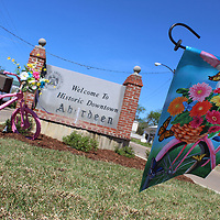 A springtime flag waves in the wind near the fountain in downtown Aberdeen. Main Street director Ann Tackett was inspired by the design and decided to place pink bicycles throughout downtown.