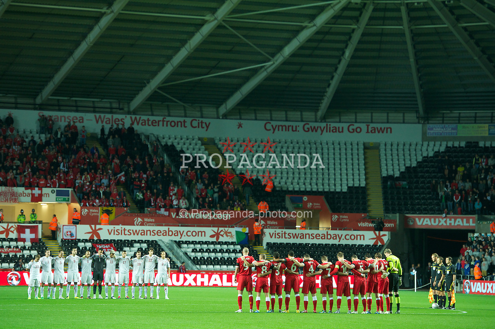 SWANSEA, WALES - Friday, October 7, 2011: Wales and Switzerland players stand to observe a minute's silence in memory of the four minors who died at the Gleision Colliery, before the UEFA Euro 2012 Qualifying Group G match at the Liberty Stadium. (Pic by Chris Brunskill/Propaganda)