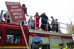 London, UK. 1st May, 2019. Steve Bray of SODEM (Stand of Defiance European Movement) uses a loud hailer to question Jeremy Corbyn (standing on top of a double-decker bus belonging to the Fire Brigades Union) about Labour Party policy on Brexit after the Leader of the Opposition spoke at a rally to coincide with the vote in Parliament on declaring a climate emergency.