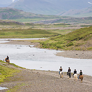 People riding horses by the river Breiðdalsá, Iceland.