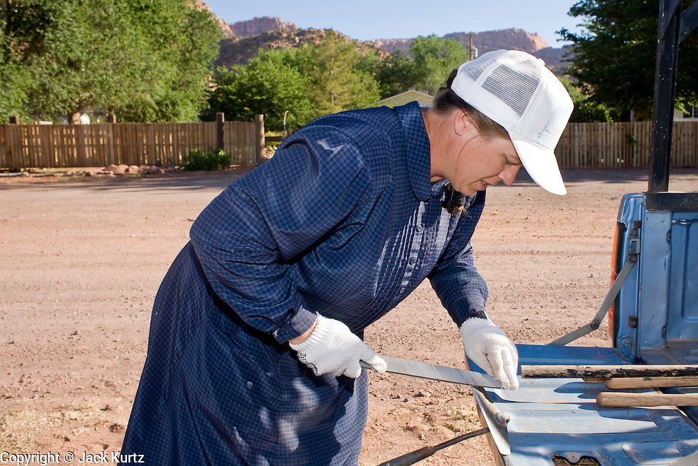"June 16, 2008 -- COLORADO CITY, AZ: A member of the Jessop family, a polygamous family and members of the FLDS, sharpens her hoe before weeding the community corn field in Colorado City. The Jessops grow about 30 percent of the food they eat and buy the rest in the community mercantile store. Colorado City and neighboring town of Hildale, UT, are home to the Fundamentalist Church of Jesus Christ of Latter Day Saints (FLDS) which split from the mainstream Church of Jesus Christ of Latter Day Saints (Mormons) after the Mormons banned plural marriage (polygamy) in 1890 so that Utah could gain statehood into the United States. The FLDS Prophet (leader), Warren Jeffs, has been convicted in Utah of ""rape as an accomplice"" for arranging the marriage of teenage girl to her cousin and is currently on trial for similar, those less serious, charges in Arizona. After Texas child protection authorities raided the Yearning for Zion Ranch, (the FLDS compound in Eldorado, TX) many members of the FLDS community in Colorado City/Hildale fear either Arizona or Utah authorities could raid their homes in the same way. Older members of the community still remember the Short Creek Raid of 1953 when Arizona authorities using National Guard troops, raided the community, arresting the men and placing women and children in ""protective"" custody. After two years in foster care, the women and children returned to their homes. After the raid, the FLDS Church eliminated any connection to the ""Short Creek raid"" by renaming their town Colorado City in Arizona and Hildale in Utah. A member of the Jessop family weeds the community corn plot in Colorado City, AZ. The Jessops are a polygamous family and members of the FLDS.   Photo by Jack Kurtz"
