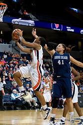 Virginia guard Monica Wright (22) jumps past Rhode Island center Whitney Hollis (41) on her way to the basket.  The Virginia Cavaliers women's basketball team defeated the Rhode Island Rams 89-53 at the John Paul Jones Arena in Charlottesville, VA on January 9, 2008.