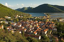 Europe, Croatia, Dalmatia, Mali Ston.  Salt pans, lush hills and village of Mali Ston, viewed from walls of 15th century fort.