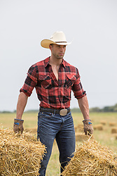 rugged cowboy with hay bales on a ranch