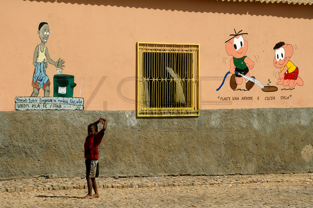 Boy walking in front of a kindergarden in Vila do Maio (Maio's village). Cape Verde population is very young and the country is known for the good use of international aid, specially in sending its students  abroad on scholarship programs.
