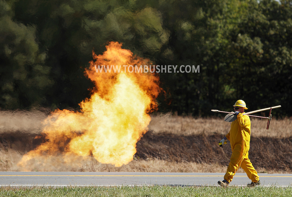 A Central Hudson worker carries tools past flames pouring out of break in a natural gas line along Route 416 in Montgomery on Monday, Sept. 24, 2012. An excavator struck the 4-inch pipeline shortly before 1 p.m. Montgomery firefighters responded and put out a brush fire caused by the fireball. The accident happened near the intersection with Route 211 by the Orange County Airport.