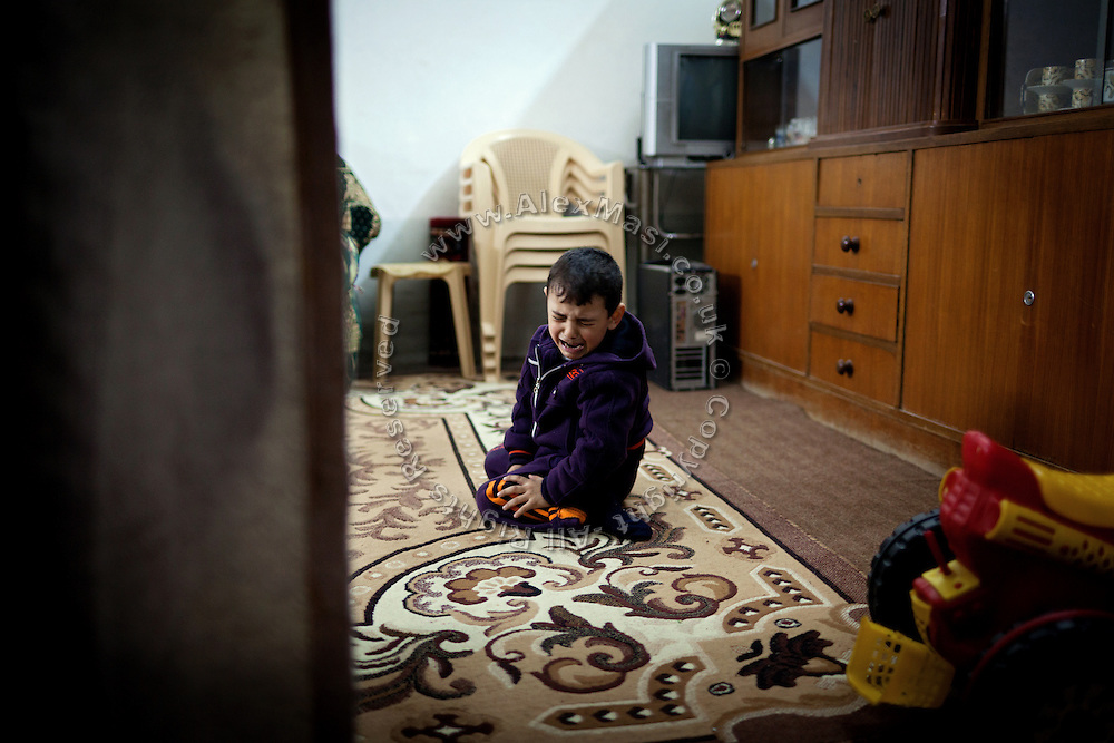 Maath, 6, a child suffering from a shortage of brain cells and mental disability, is crying on the floor of his home in Fallujah, Iraq. The parents and their relatives have no history of birth defects.