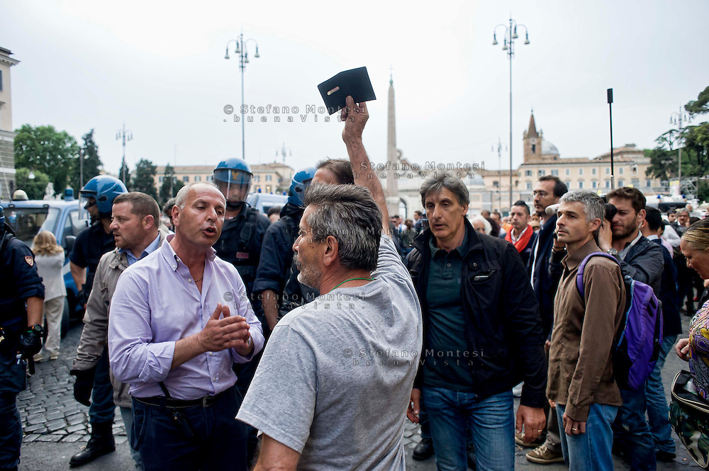Roma, 12 Maggio  2014<br /> Manifestazione dei Movimenti per il diritto all&rsquo;abitare hanno contestato il Presidente del Consiglio Matteo Renzi che parlava sul palco di piazza del Popolo per la manifestazione conclusiva del Partito Democratico in vista delle elezioni europee di domenica. Attivisti dei Movimenti per la Casa sono stati  fermati dalla Polizia.Nella foto: Manifestante mostra il documento d'identit&agrave; alla polizia<br /> Rome, May 12, 2014 <br /> Manifestation of the movements for housing rights, objected to the Chairman of the Board, Matteo Renzi, who spoke on stage at the Piazza del Popolo to the closing event of the Democratic Party in the European elections on Sunday. Activists of the Movement for the House were stopped by the police. In pictures: Protestor shows the identity document  to the police