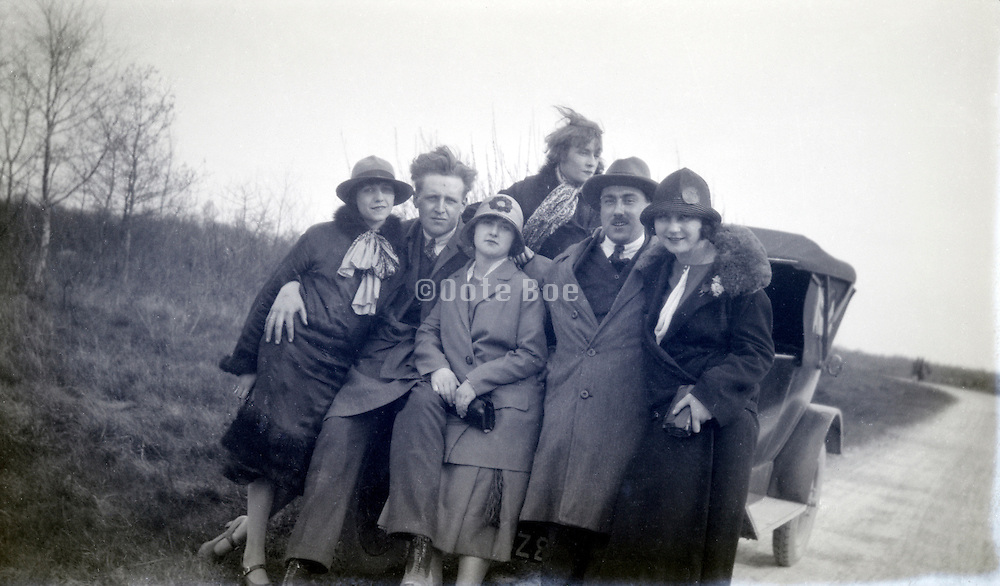 family with friends posing in front of the car on a rural countryside road 1920s