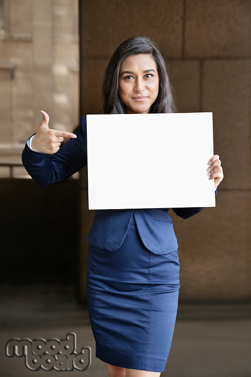 Portrait of a young Indian businesswoman pointing towards Moodboard sign