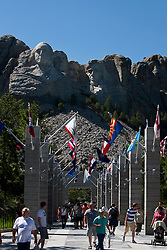View of Mt. Rushmore with visitors walking along flags of the United States, Mount Rushmore National Monument, South Dakota, United States of America