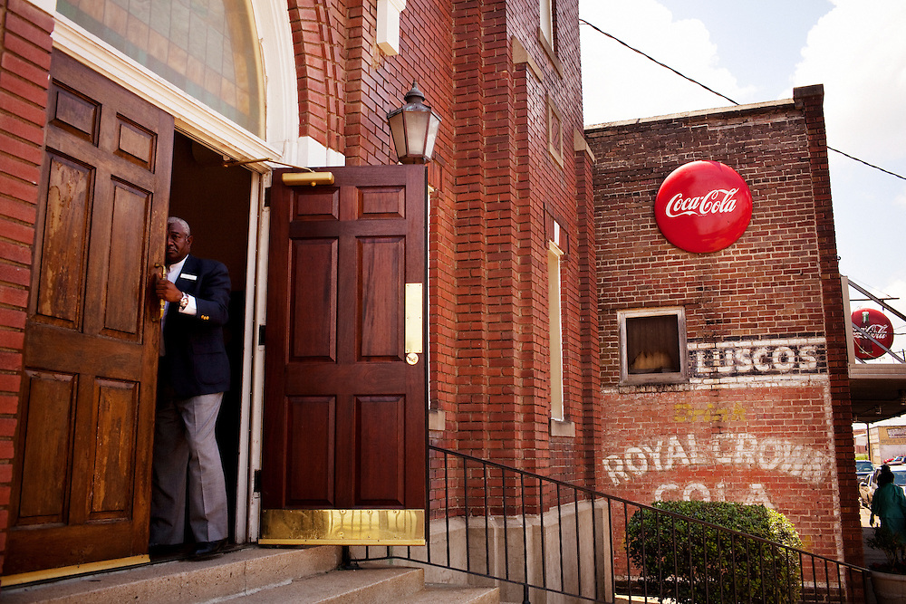 A deacon opens the doors of Mt. Zion Missionary Baptist Church, just across the tracks from the Baptist Town neighborhood of Greenwood, Mississippi on Sunday, May 23, 2010 as the service lets out.