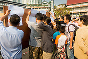 26 JANUARY 2014 - BANGKOK, THAILAND: Prospective voters look up their names of a list of registered voters at the Wat That Thong polling place in Bangkok. They did not get to vote because the polling place was shut down by anti-government protestors. Early voting was supposed to be Sunday January 26 but blocked polling places left hundreds of thousands of people unable to vote casting the February 2 general election into doubt and further gridlocking Thai politics. Anti-government protestors forced the closure of polling places in Bangkok Sunday as a part of Shutdown Bangkok. Protestors blocked access to gates and entry ways to polling places and election officials chose the close them rather than confront protestors. Shutdown Bangkok has been going for 12 days with no resolution in sight. Suthep, the leader of the anti-government protests and the People's Democratic Reform Committee (PDRC), the umbrella organization of the protests,  is still demanding the caretaker government of Prime Minister Yingluck Shinawatra resign, the PM says she won't resign and intends to go ahead with the election.    PHOTO BY JACK KURTZ
