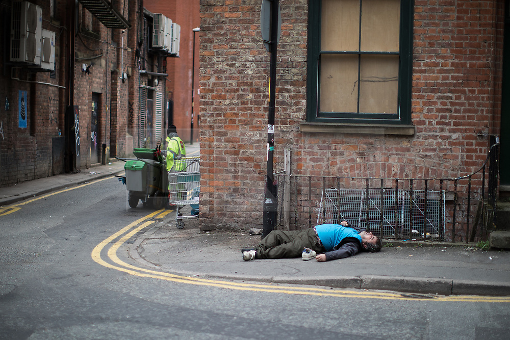 © Licensed to London News Pictures . 06/04/2017 . Manchester , UK . A man lies collapsed on the pavement on Newton Street . An epidemic of abuse of the drug spice by some of Manchester's homeless population , in plain sight , is causing users to experience psychosis and a zombie-like state and is daily being witnessed in the Piccadilly Gardens area of Manchester , drawing large resource from paramedic services in the city centre . Photo credit : Joel Goodman/LNP