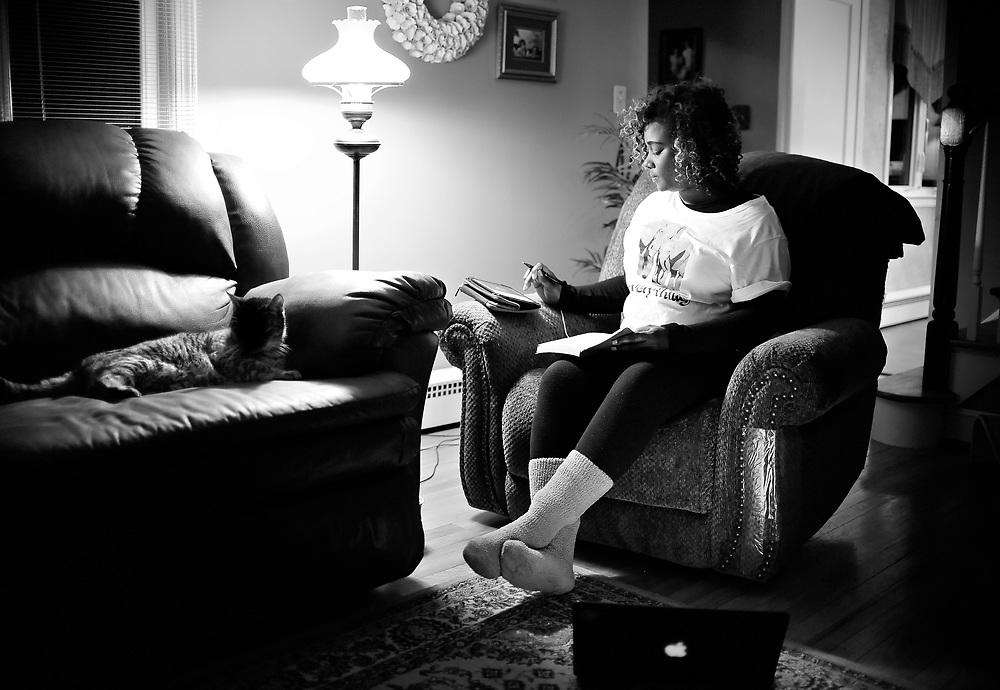 Nekita Waller writes lyrics to a song she listens to on her iPad.