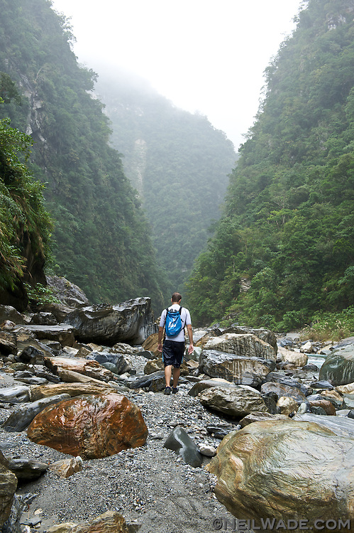 A river tracer navigates through a narrow river valley near Taroko Gorge, Taiwan.