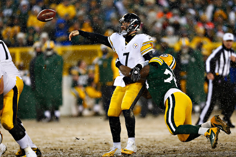 GREEN BAY, WI - DECEMBER 22:  Ben Roethlisberger #7 of the Pittsburgh Steelers throws a pass away while being hit by Mike Daniels #76 of the Green Bay Packers at Lambeau Field on December 22, 2013 in Green Bay, Wisconsin.  (Photo by Wesley Hitt/Getty Images) *** Local Caption *** Ben Roethlisberger; Mike Daniels