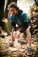 A man bent over taking a rest on a trail run through a forest in Autumn colors.