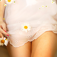 Girl in dress with daisies floating around her legs and dress lying in bath