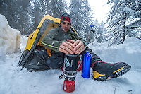 A male mountaineer, as seen preparing a warm beverage in a small and portable gas stove on a cold Winter day in Aosta Valley, Italy.
