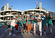 A group of Miami Dolphins fans wearing team gear and colors poses for a pregame photo with Sun Life Stadium standing tall in the background during the NFL week 14 regular season football game against the New York Giants on Monday, Dec. 14, 2015 in Miami Gardens, Fla. The Giants won the game 31-24. (©Paul Anthony Spinelli)