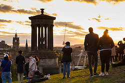 Tourists gather on Calton Hill to watch the sunset over Edinburgh, Scotland, United Kingdom.