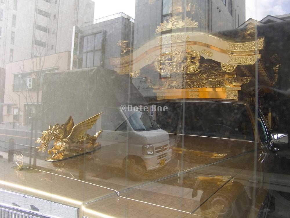 elaborate Japanese funeral car behind a window
