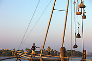 The Chinese fishing nets at the harbour of Fort Cochin are fixed land based installations for an unusual form of fishing.<br /> Huge mechanical contrivances hold out horizontal nets up to 20m or more across. Each structure is at least 10 m high and comprimises a cantilever with an outstreched net suspended over the sea and large stones suspended from ropes as counterwight at the other end.<br /> Each installation is operated by a team of up to six fishermen.<br /> The system is sufficiently balanced that the weight of a man walking along the main beam is sufficient to cause the net to descend into the sea.<br /> The net is left for a short time, a few minutes, before it is raised by pulling on ropes.<br /> Rocks, each 30 cm or so in diameter are suspended from ropes of different lengths. As the net is raised, some of the rocks one by one come to rest on a platform thereby keeping everything in balance.<br /> The Chinese fishing nets have become a very popular tourist attraction.<br /> Fort Cochin, Kerala, India 2013<br /> &copy;Ingetje Tadros