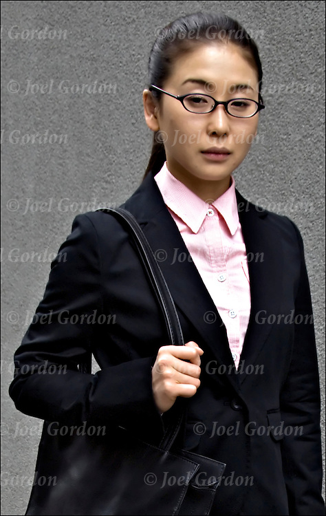 Portrait of Asian (Japanese) woman wearing business suit talking on cell phone