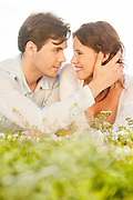 Affectionate man touching woman while looking at her on grass