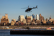 A silhouetted helicopter comes into land in the Downtown Manhattan/ Wall Street Heliport; Pier 6, Manhattan, New York City, New York, United States of America. Another helicopter waits on the helipad. Brooklyn borough can be seen in the background.   (photo by Andrew Aitchison / In pictures via Getty Images)