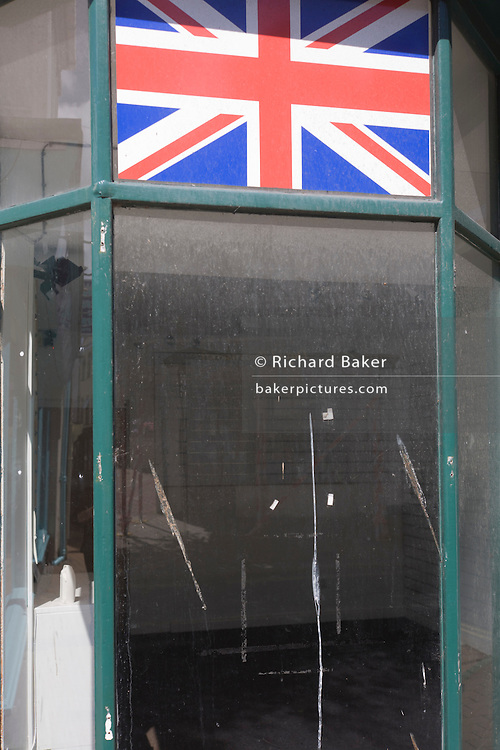 A Union Jack flag hangs above white emulsion paint which has been smeared over a shop window in Lavender Hill, Battersea, a victim of the UK recession. Around a recession-bled Britain, high-street businesses have been going bust in their thousands. Britain has now endured eight recessions since the Second World War. No two recessions are alike, and that applies to the current slowdown also. It has been caused by a shock to the availability of credit, a massive build up of debt. The number of people out of work currently stands at almost two million. Given the rate at which the economy is deteriorating this could easily be above three million. From a continuing piece of work about windows and urban messages, the picture is from the project of closed business windows: 'Bust - the Art of Recession'.