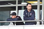 Roelof van der Merwe and Lewis Gregory of Somerset look glum as he peer out from the team balcony during the delay the start of play after a heavy rain shower this morning ahead of the Specsavers County Champ Div 1 match between Somerset County Cricket Club and Essex County Cricket Club at the Cooper Associates County Ground, Taunton, United Kingdom on 26 September 2019.
